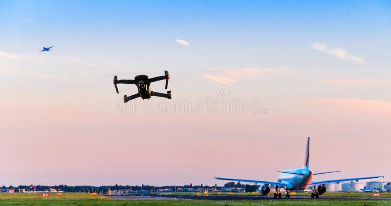 Vuelo sin tripulación del abejón cerca de la pista en el aeropuerto mientras que el aeroplano comercial saca llevar a la colisión imágenes de archivo libres de regalías