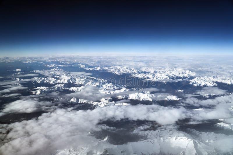 Vuelo sobre los glaciares alpinos en un día en parte nublado fotografía de archivo