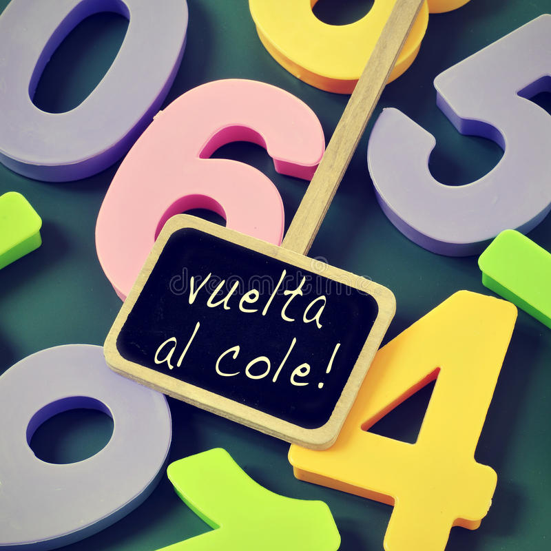 Vuelta al cole, back to school in spanish. Sentence vuelta al cole, back to school in spanish, written in a blackboard label and a pile of numbers of different stock photo