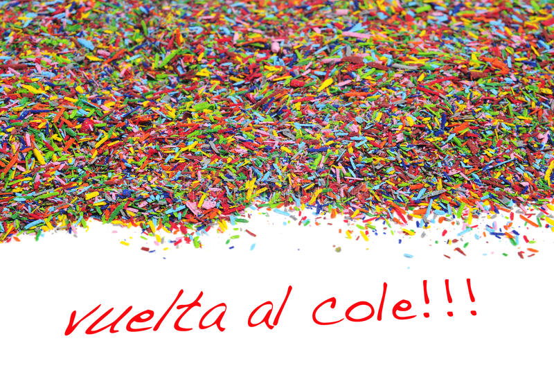 Vuelta al cole, back to school written in spanish. On a white background and a pile of crayon shavings of different colors stock photo