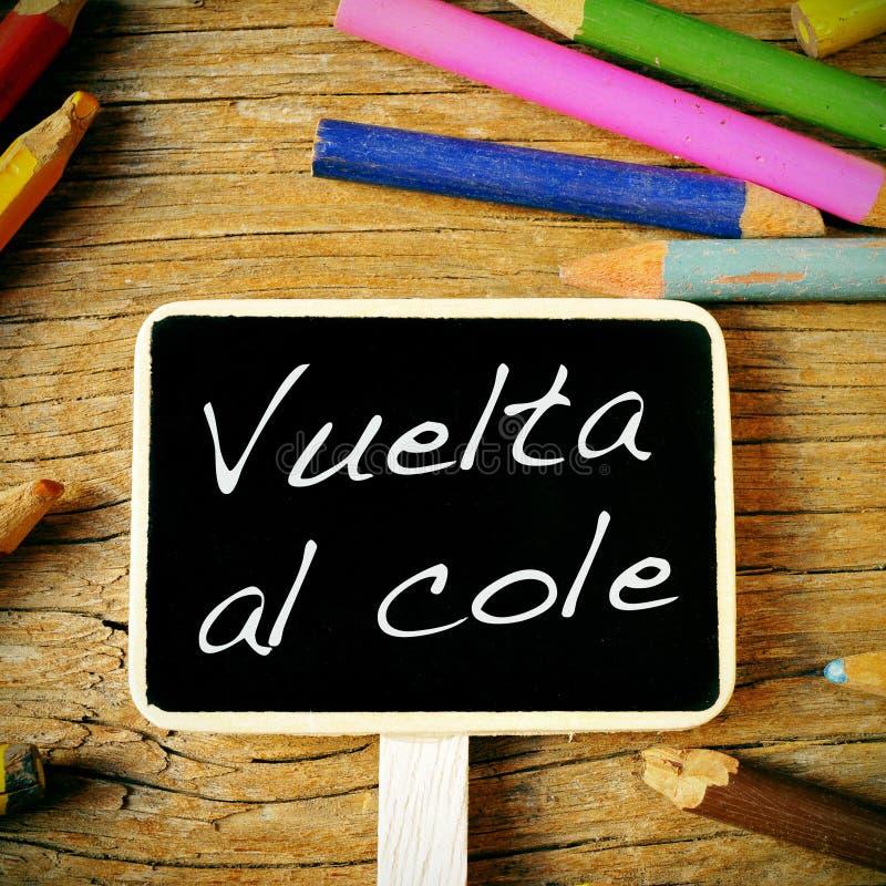 Vuelta al cole, back to school written in spanish. The sentence vuelta al cole, back to school written in spanish in a blackboard label, on a wooden desk and stock photo