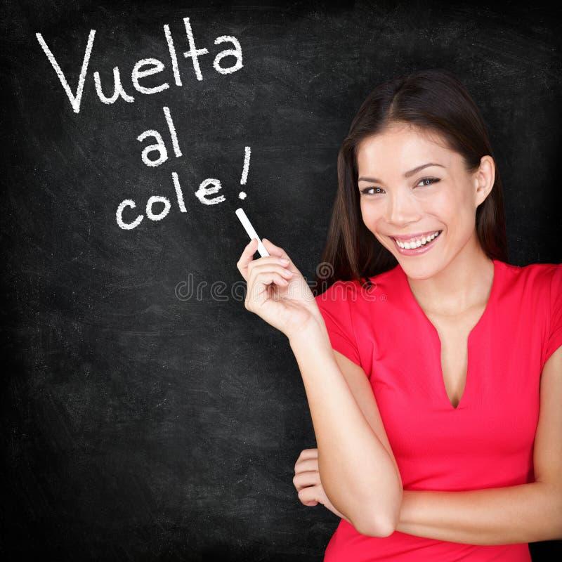Vuelta al cole - Spanish teacher back to school. Written in Spanish on blackboard by woman teacher holding chalk. Smiling happy woman teaching Spanish language stock photography