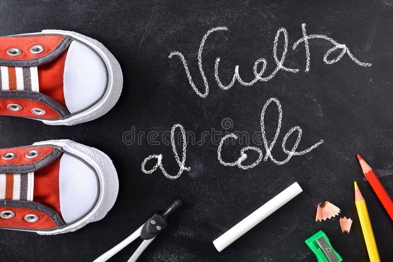 Vuelta al cole written on a blackboard with tools. Back to school concept. Vuelta al cole written with chalk on a blackboard and school supplies and sneakers royalty free stock photo