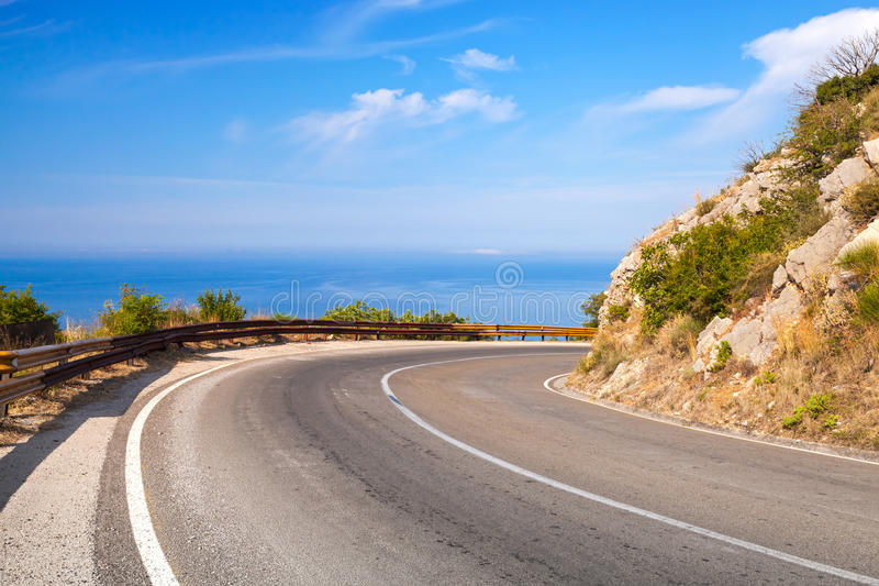 Vuelta de la carretera de la montaña con el cielo azul y el mar imagen de archivo