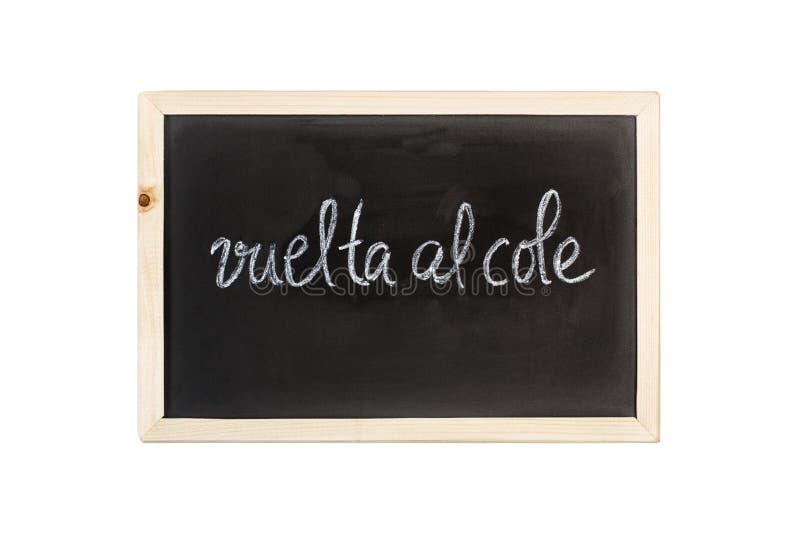 Vueltaal cole terug naar schoolwoorden schrijft in krijt op een bord stock afbeelding