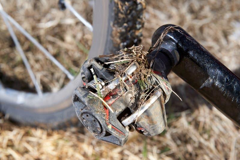 Vuil fietspedaal in close-upmening stock afbeelding
