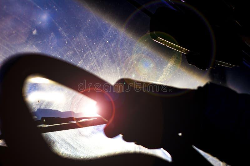 Vuil gekrast autowindscherm met wisser door vaag stuurwiel met de hand van de bestuurder op vage achtergrond stock foto