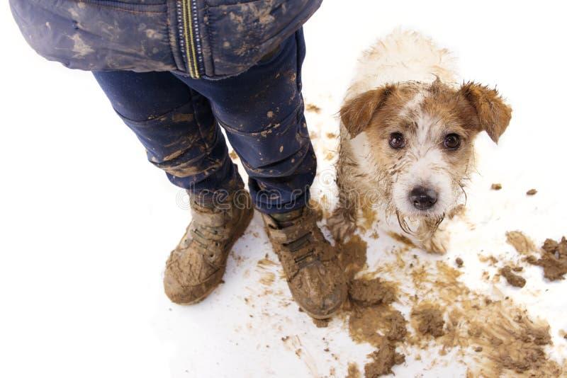 Vuil hond en jong geitje Schuldige hefboom Russell en jongen die modderige doek en schoenen dragen Ge?soleerdj op witte achtergro royalty-vrije stock afbeeldingen