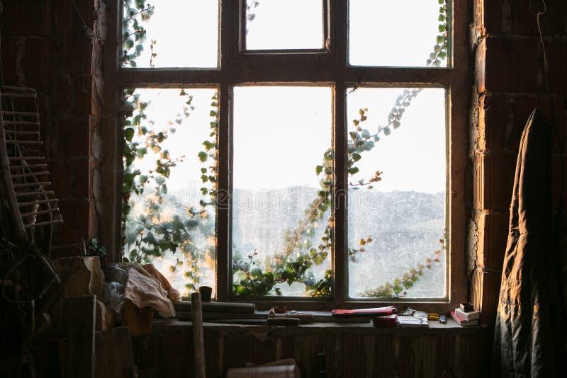 Vuil oud venster en de avondzonnestraal royalty-vrije stock afbeelding