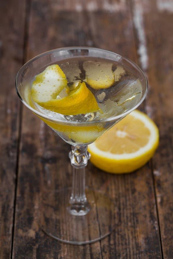 Vuile die martini met een citroendraai wordt gekoeld en wordt versierd op houten lijst stock afbeeldingen
