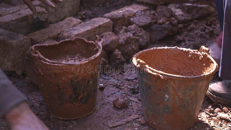 Vuile emmer met klei, grond ter plaatse voor de bouw van het modderhuis royalty-vrije stock foto