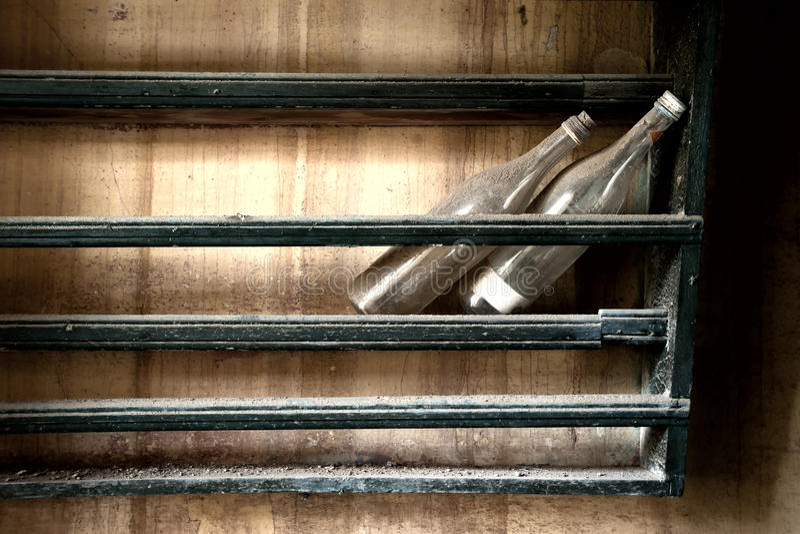 Vuile flessen op stoffige plank stock afbeeldingen