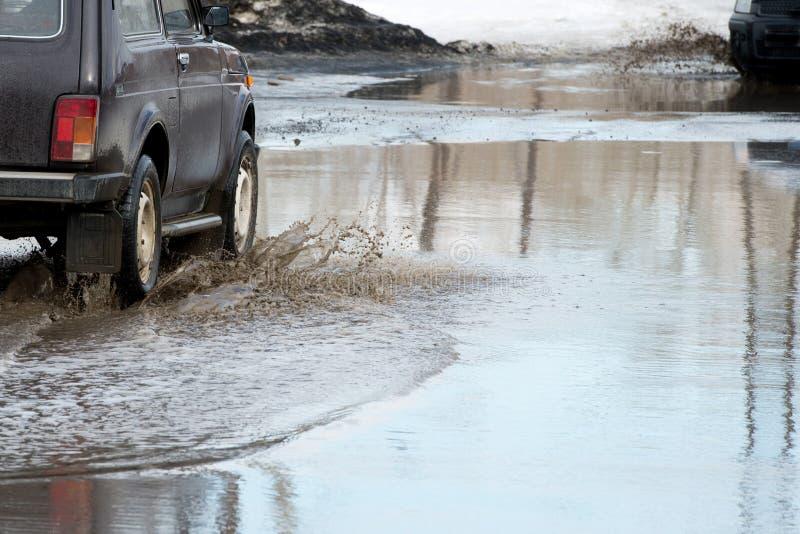 Vuile golf van nevel van onder de wielen van een vrachtwagen Water op de weg Nevel van onder de wielen van auto's stock foto's
