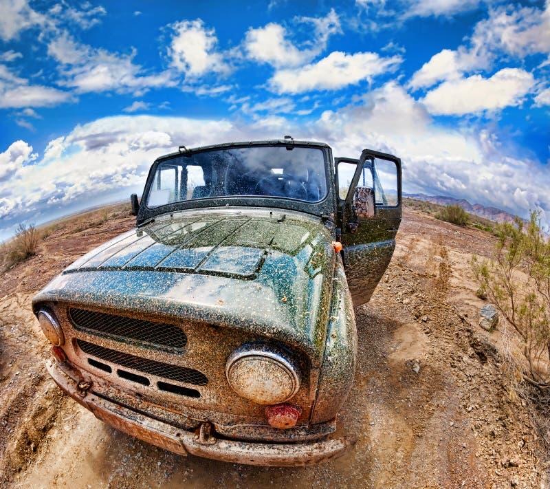 Vuile jeep in woestijn royalty-vrije stock afbeelding