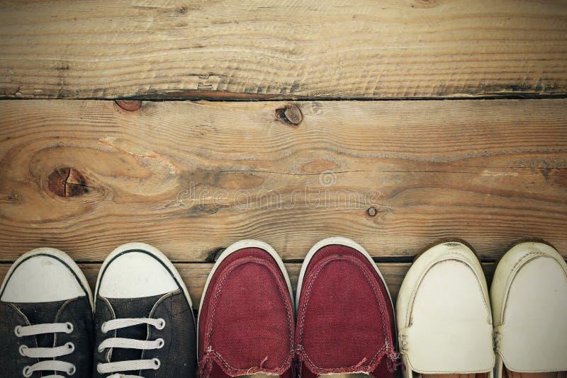 Vuile oude schoenen op houten vloer, met exemplaarruimte Hoogste mening stock afbeeldingen