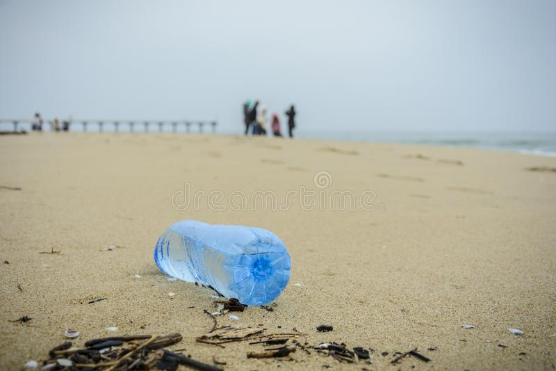 Vuile plastic die fles op het strand wordt gelaten vallen stock foto's