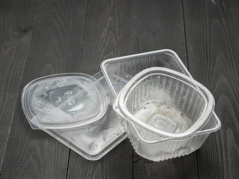 Vuile plastic voedselcontainer op donkere houten achtergrond stock foto