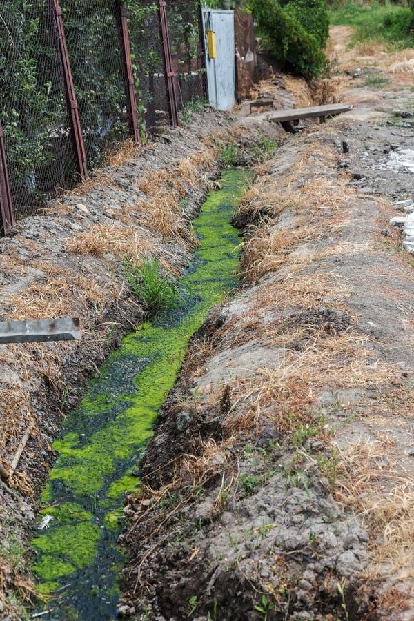 Vuile riolering samen met riolering in een open sloot langs de straat Vuile drainage, een open rioolcollector hier met giftige al royalty-vrije stock afbeelding