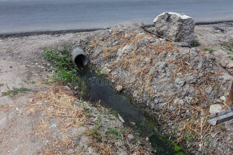 Vuile riolering samen met riolering in een open sloot langs de straat Vuile drainage, een open rioolcollector hier met giftige al royalty-vrije stock foto