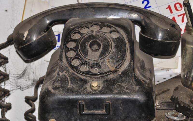 Vuile stoffige zwarte oude telefoon in de workshop royalty-vrije stock afbeelding