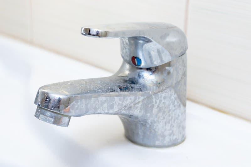Vuile tapkraan met limescale, verkalkte waterkraan met kalkschaal op waskom in badkamers stock afbeelding