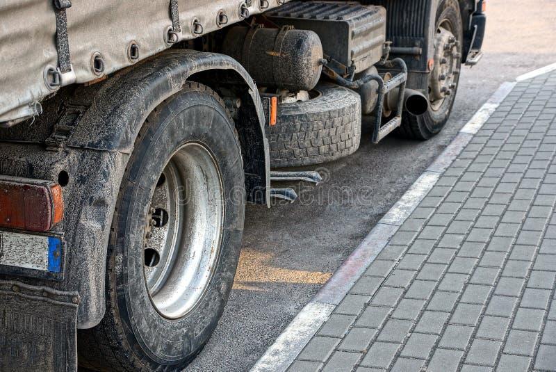 Vuile wielen van een grote vrachtwagen op een grijs asfalt royalty-vrije stock afbeelding
