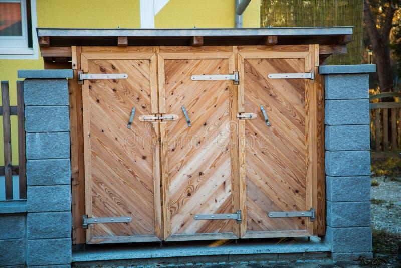 Vuilnisbakken in houten geval, huisvuilhuis stock afbeelding