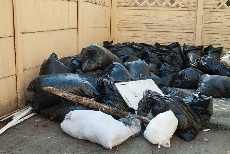 Vuilniszakken in yard Een stapel van zwart-witte plastic vuilniszakken royalty-vrije stock afbeelding