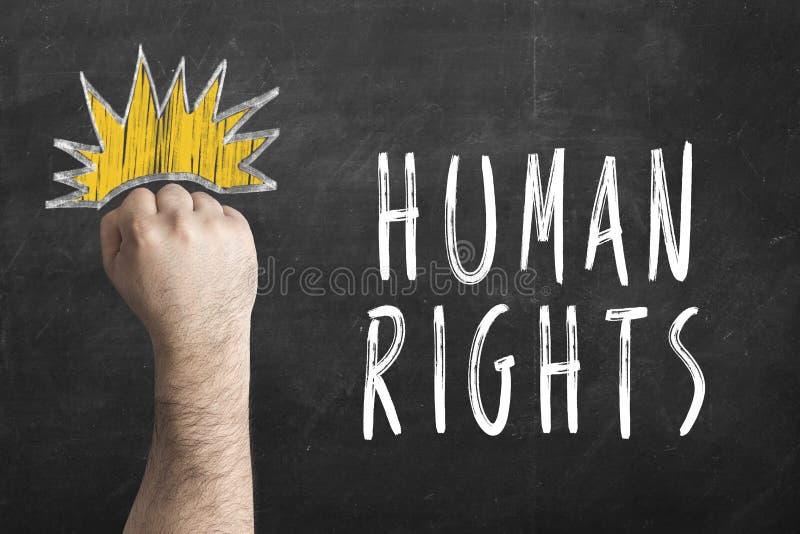 Vuist en inschrijvingsrechten van de mens op bord Internationale Rechten van de mensdag stock foto's