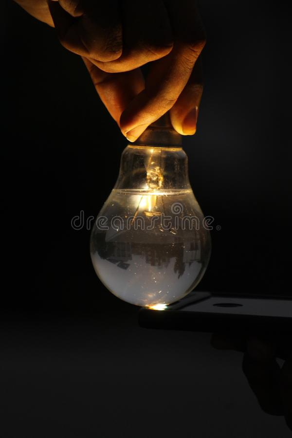Vul water in gloeilamp en gloed geel licht stock afbeelding
