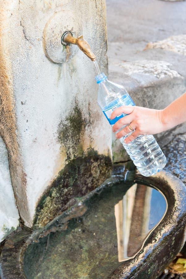 Vul waterfles vanaf een hydrantfontein royalty-vrije stock foto's