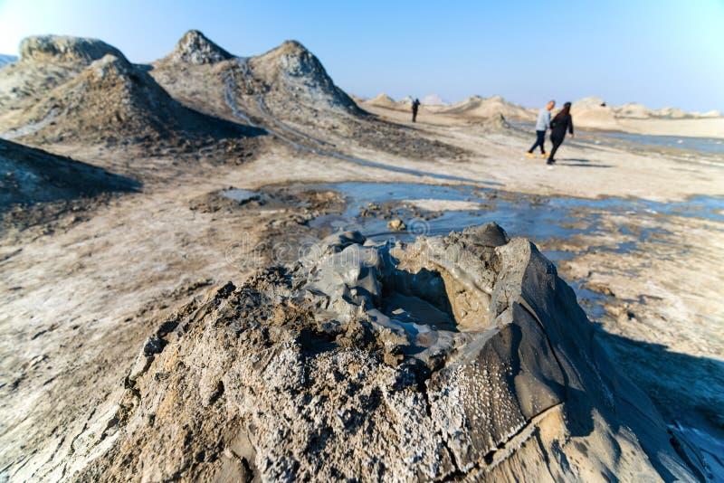 vulcão de lama com antecedentes turísticos no parque nacional do gobustão, Azerbaijão Cratera borbulhante de um vulcão de lama fotografia de stock royalty free