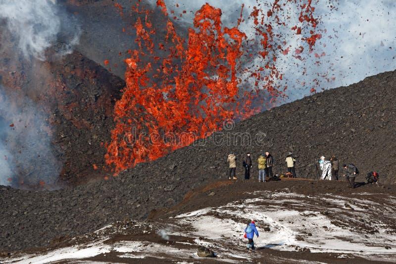 Vulcão de Tolbachik da erupção em Kamchatka, turistas na lava da fonte do fundo que escapa do vulcão da cratera imagem de stock royalty free