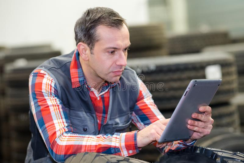 Vulcanizing shop worker using tablet royalty free stock photos