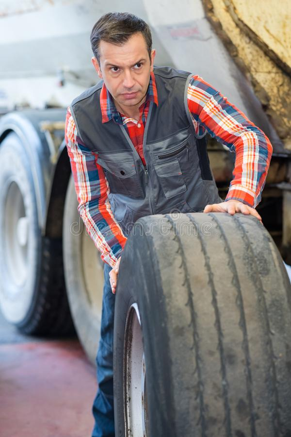 Vulcanizing worker rolling tire royalty free stock image