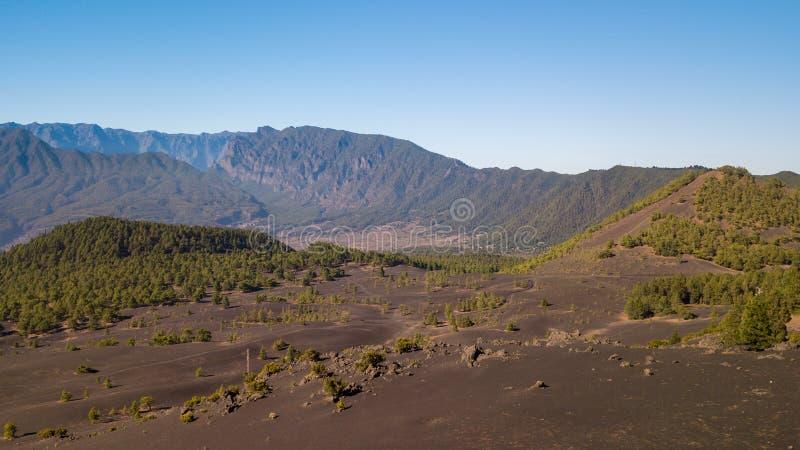 Vulkaanlandschap en dennenbos in astronomisch perspectief stock fotografie