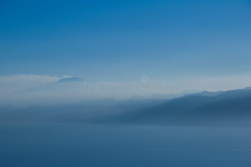 Vulkan och berg i misten. royaltyfri bild