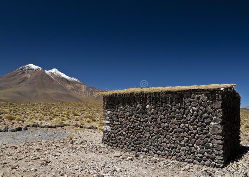 Vulkan und eine Steinhütte stockbilder