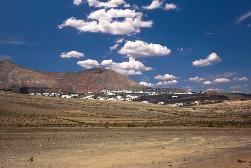 Vulkanische krater dicht bij La Caleta, Famare onder een blauwe hemel met wolken Lanzarote, Canarische Eilanden, Spanje royalty-vrije stock afbeeldingen