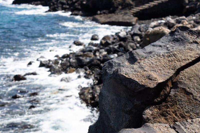 Vulkanische rots dichte omhooggaand met het rotsachtige strand op de achtergrond, Tenerife, Canarische Eilanden, Spanje - Beeld stock fotografie
