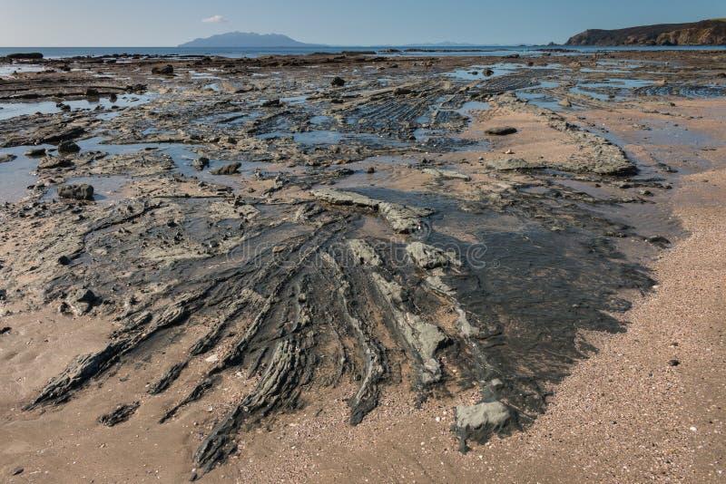 Vulkanische rotsvormingen op strand in Omaha Bay stock afbeeldingen