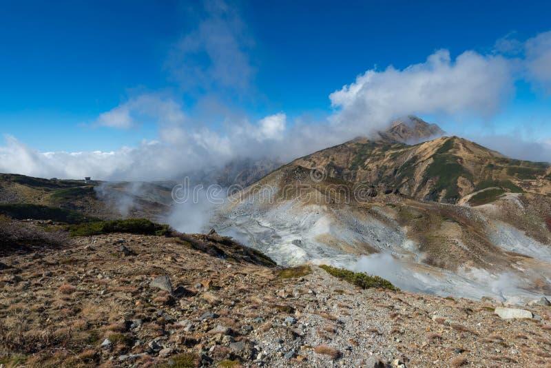 Vulkaniska lufthål med rök och berg med blå himmel, sulphur och askaen Murodo Japan fjällängar arkivfoton