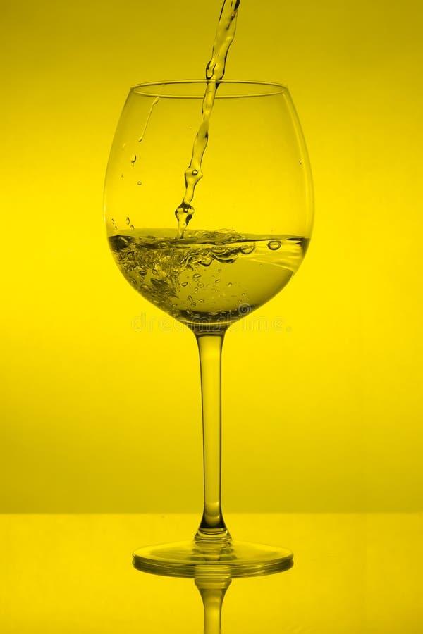 Vullend wijnglas op gele achtergrond, die wijnglas gieten royalty-vrije stock afbeeldingen