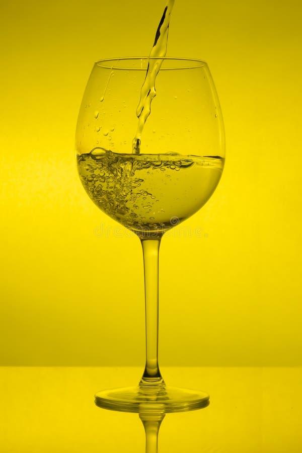 Vullend wijnglas op gele achtergrond, die wijnglas gieten stock fotografie
