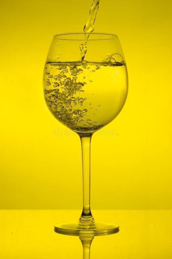 Vullend wijnglas op gele achtergrond, die wijnglas gieten royalty-vrije stock fotografie