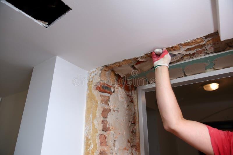 Vullende muren en assemblage en het lijmen van gipsraad tijdens vernieuwing van een ruimte royalty-vrije stock foto