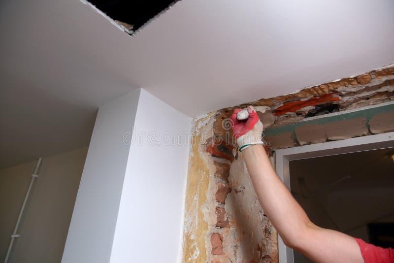 Vullende muren en assemblage en het lijmen van gipsraad tijdens vernieuwing van een ruimte stock afbeeldingen