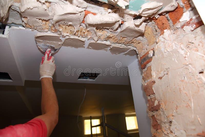 Vullende muren en assemblage en het lijmen van gipsraad tijdens vernieuwing van een ruimte royalty-vrije stock foto's
