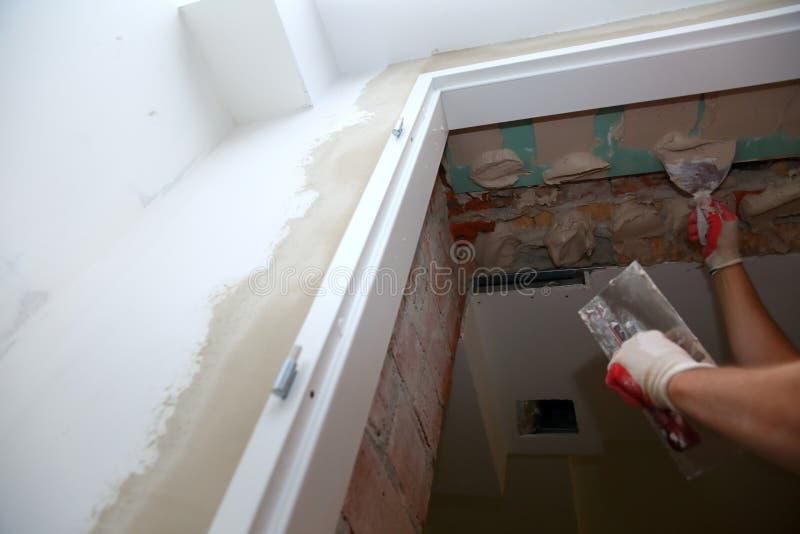 Vullende muren en assemblage en het lijmen van gipsraad tijdens vernieuwing van een ruimte royalty-vrije stock afbeelding
