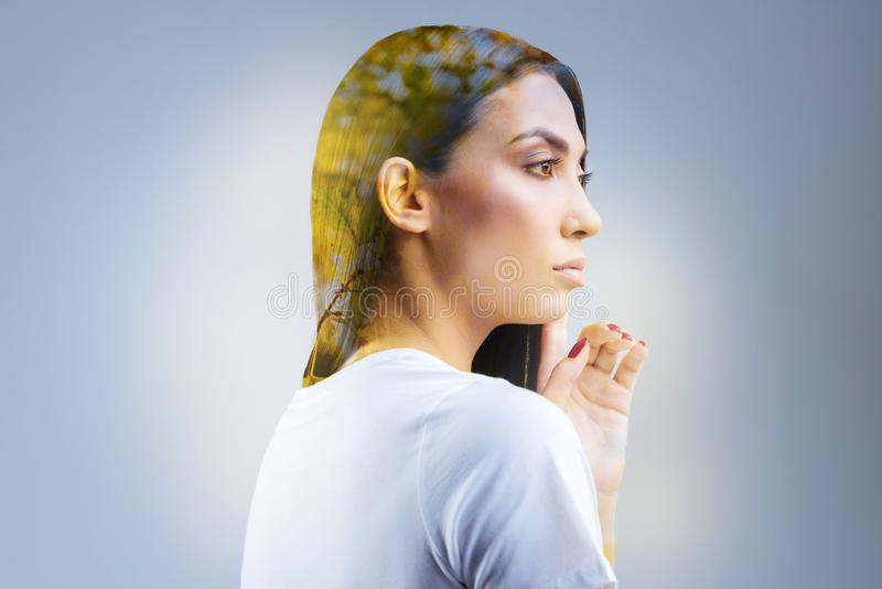 Good looking tender woman getting inspiration. Vulnerable nature. Kind brunette musing woman experiencing doubts while turning in profile and touching her chin royalty free stock photos